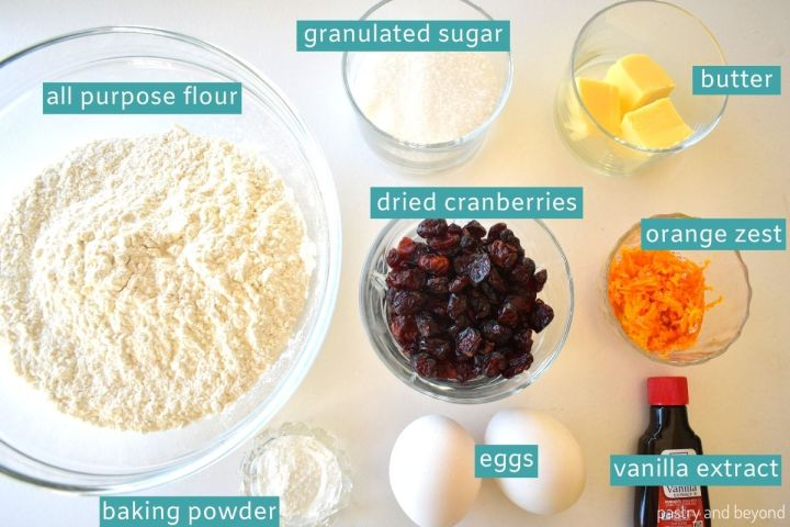 Ingredients of cranberry orange biscotti on a white surface.