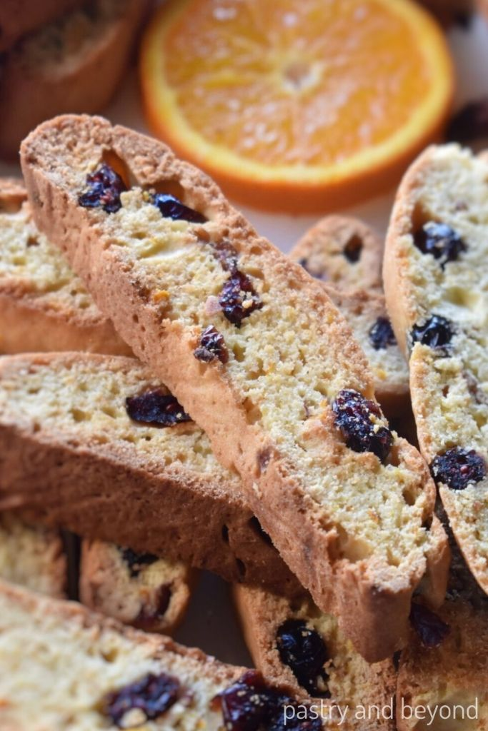 Orange cranberry biscotti slices with a slice of orange in the background.