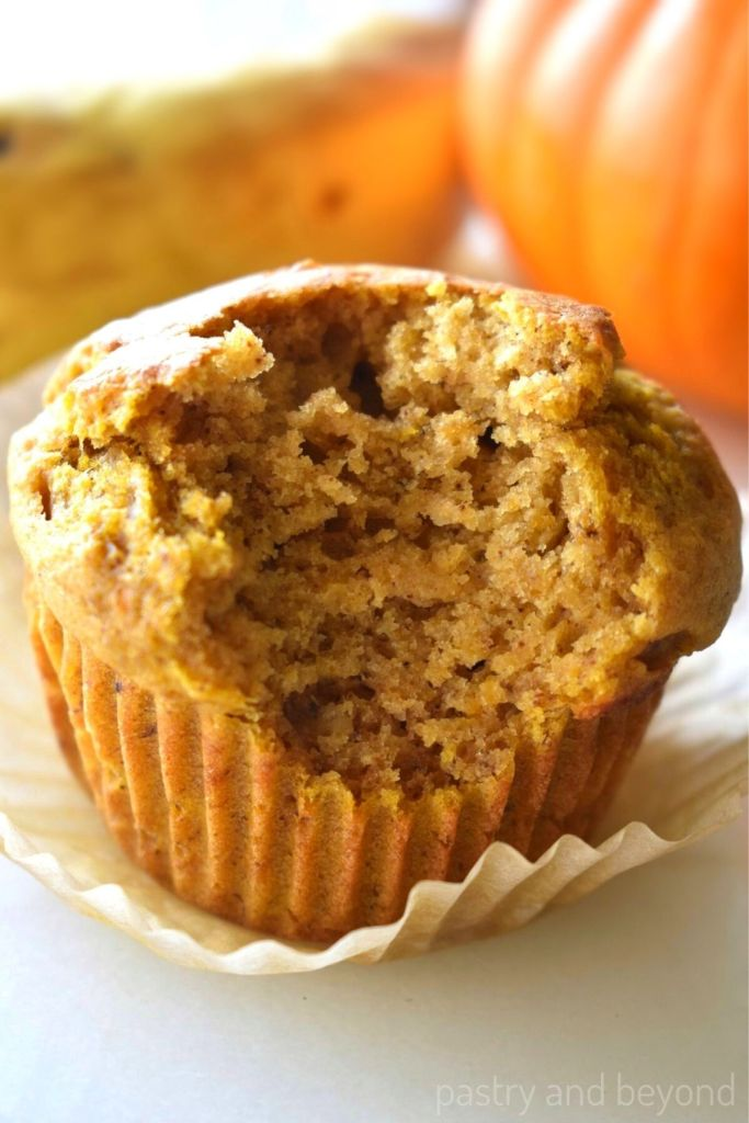 Pumpkin banana muffin with a bite taken from it.