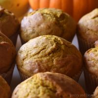 Pumpkin banana muffins with banana and pumpkin in the background.