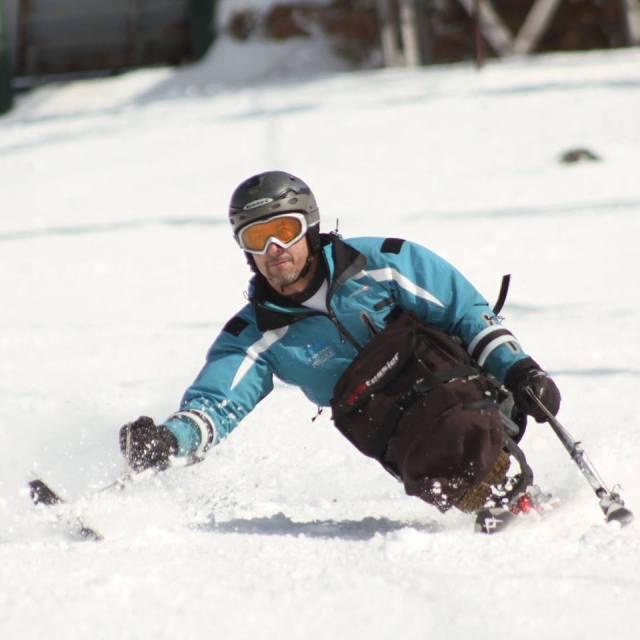 Germán Vega, el primer instructor de esquí en silla de ruedas del mundo, descendiendo de la montaña con equipos adaptados.
