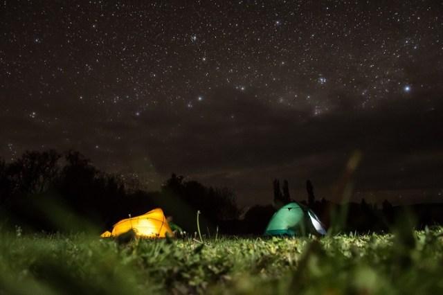 Dos carpas en la noche debajo de un cielo estrellado.