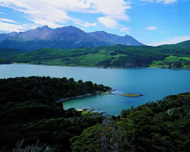 Vista panorámica del lago, rodeado de bosques verdes y montañas de fondo. Tierra del Fuego en verano.