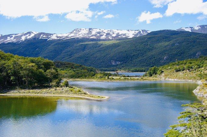 Vista desde arriba de un lago con montañas detrás en Tierra del Fuego en verano