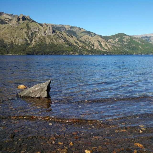 Vista desde la costa del lago, agua transparente y sierras de fondo.