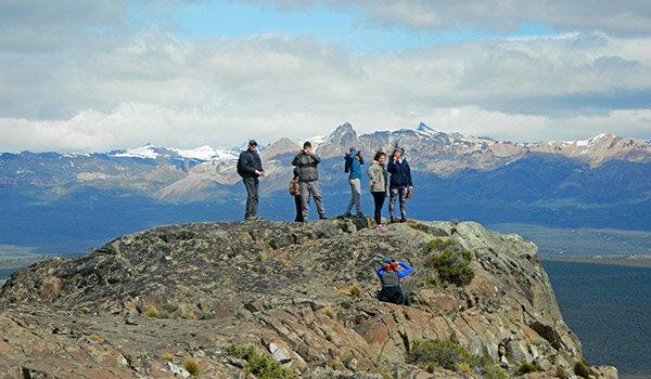 Grupo de personas sobre una roca, observando desde las alturas.