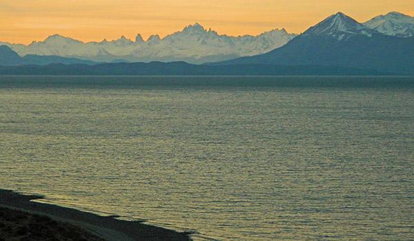 Lago y montañas de fondo al atardecer.