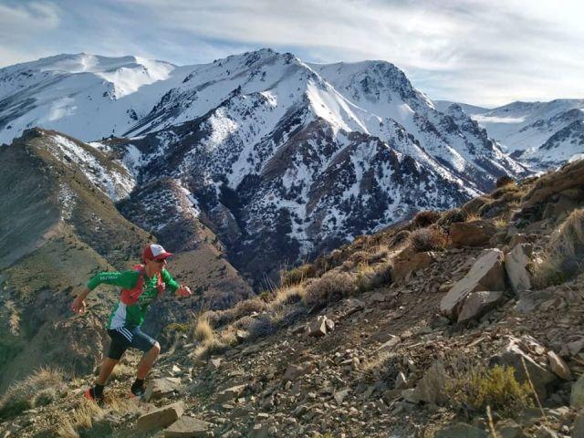 Hombre subiendo a la cima de la montaña. Esquel y Trevelin se posicionan para el verano.