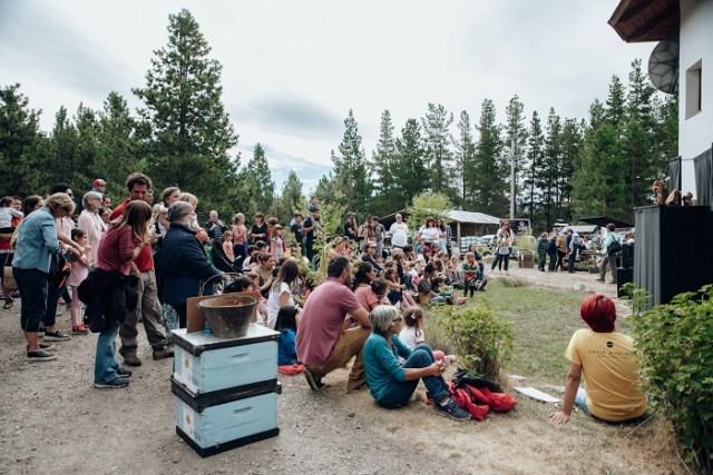 Grupo de personas escuchando una charla en el predio donde se fabrica la miel.