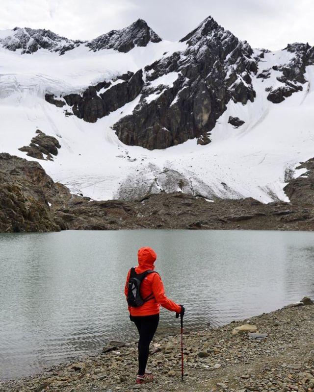 Mujer mirando a la montaña con el glaciar.