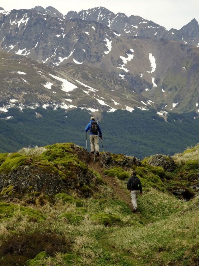 Dos personas subiendo la montaña con bastones y equipo de senderismo.