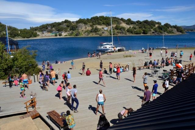 Grupo grande de personas tomando clases de gimnasia en la costa. Fiesta del Lago y las Araucarias.