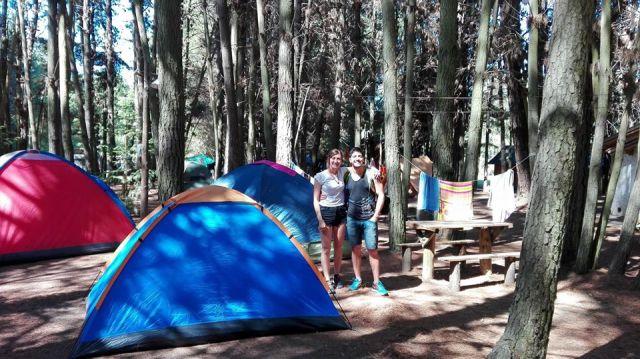 Pareja en medio del bosque con carpas en el camping La Chacra de El Bolsón.