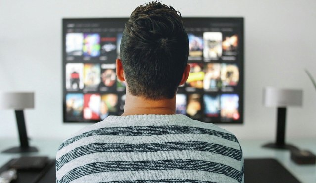 Hombre mirando películas en la televisión.