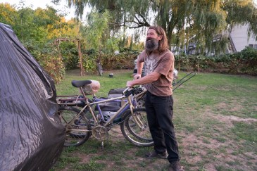 Perry bikes around with a tarp-covered trailer picking up discarded objects for the garden.