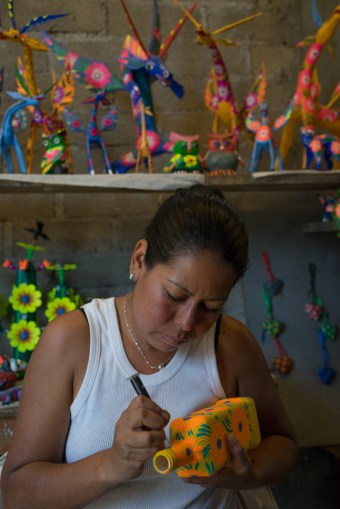Sisters Isabel Gomez Santiago and Gloria Ines Gomez Santiago paint alebrijes in Arrizola, a small town outside of Oaxaca. This is Isabel using a hypodermic needle to make dots.