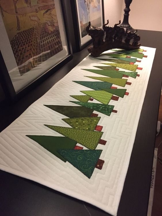 Amino de mesa en patchwork con abetos navideños verdes aplicados sobre fondo blanco y acolchados a máquina