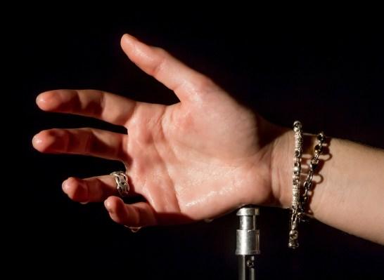 L'eau sur la main crée des reflets spéculaires blancs.