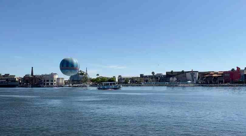 Imagem do lago com barco do transporte da Disney ao fundo com Disney Springs mais ao fundo.