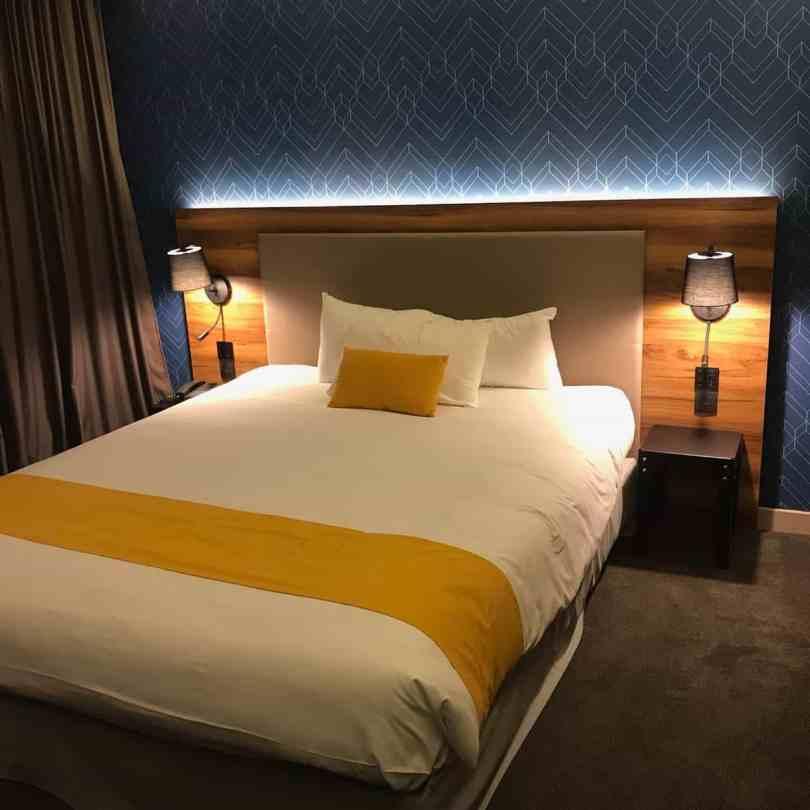 Foto de um dos quartos do Hotel lÉlysee Val d'Europe com cama confortável e decoração moderna.