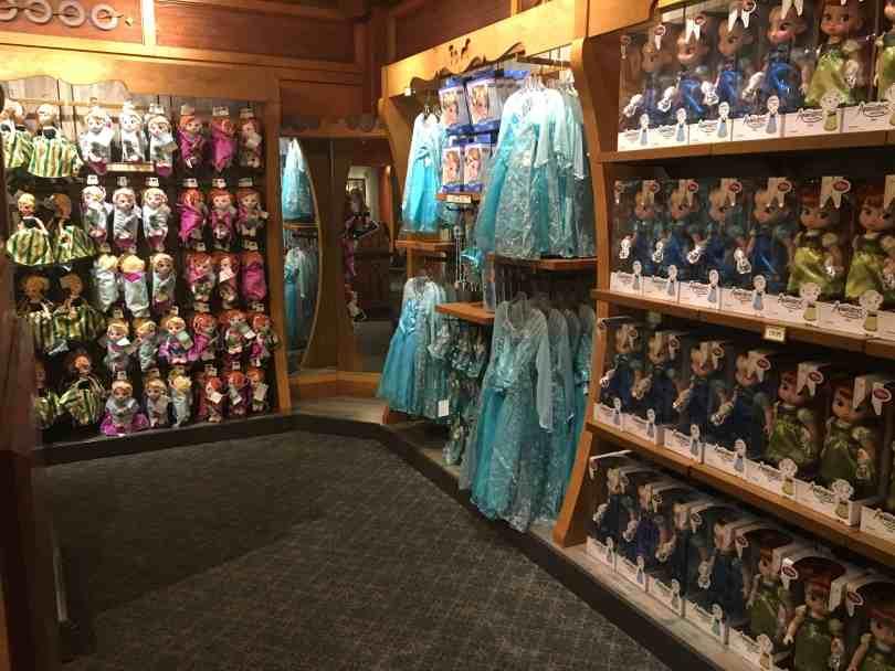 Foto de interior de loja da Disney nos parques com prateleiras repletas de bonecas de o princesas.
