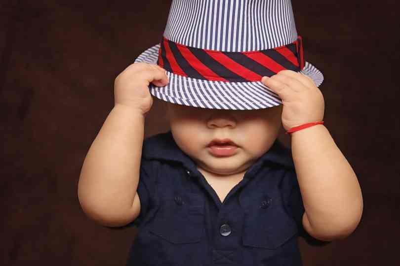 Vale olhar para as roupas e acessórios para bebês, como o chapéu e a camisa que aparecem nesse bebê da foto!