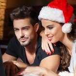 Happy young couple online shopping for christmas, sexy woman in red santa hat