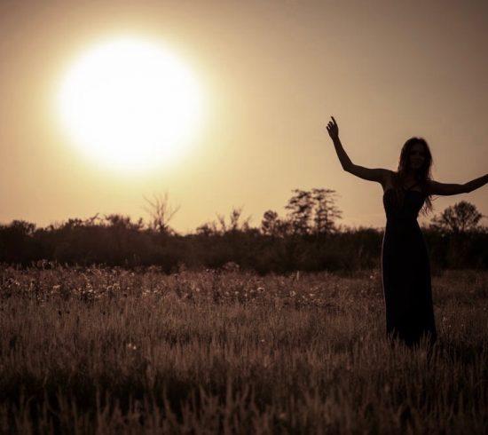 Silueta de niña bailando en vestido contra el cielo del atardecer