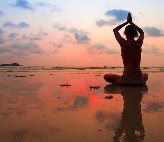 Silhouettieren Sie die junge Frau praktizieren Yoga am Strand bei Sonnenuntergang