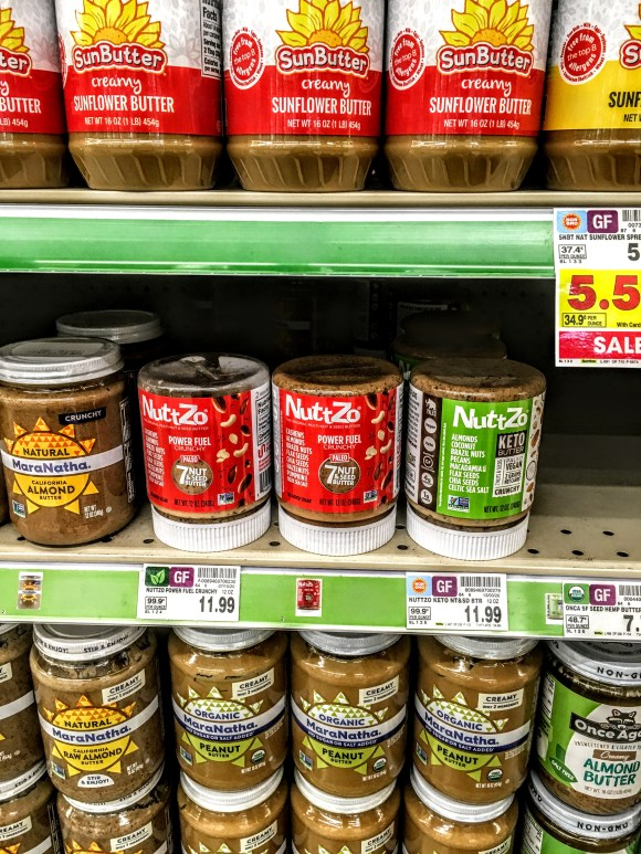 A store shelf displaying peanut butters, including Nutzzo Keto Butter.