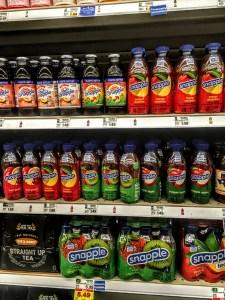 A shelf displaying bottles of Snapple Mango Madness.