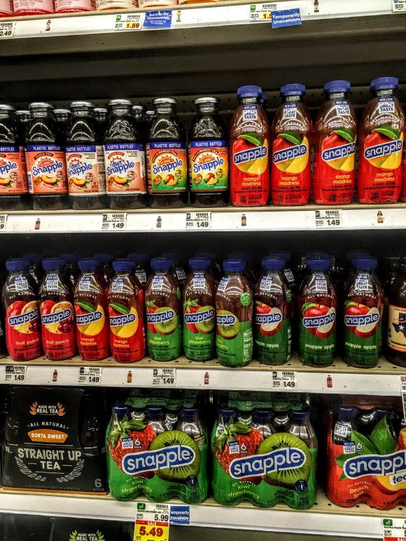 A store shelf displaying bottles of Snapple Mango Madness.