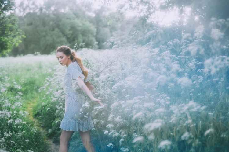 gentle woman walking on path in field with blooming flowers