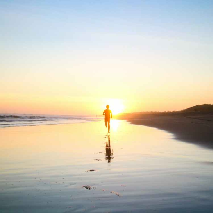 silhouette of boy running in body of water during sunset