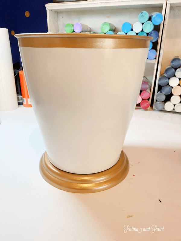 white and gold wastebasket