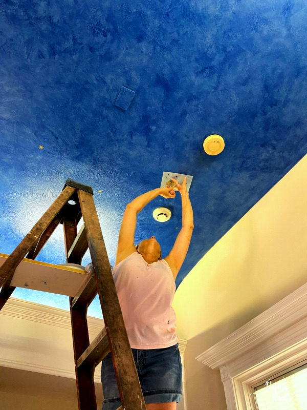 woman putting stars on ceiling