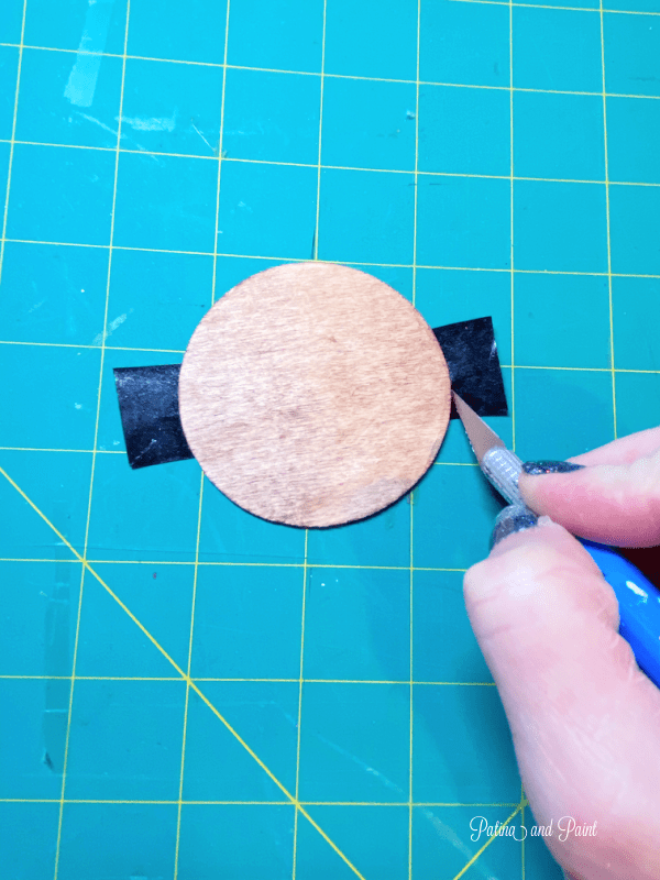 cutting off tape around wooden circle