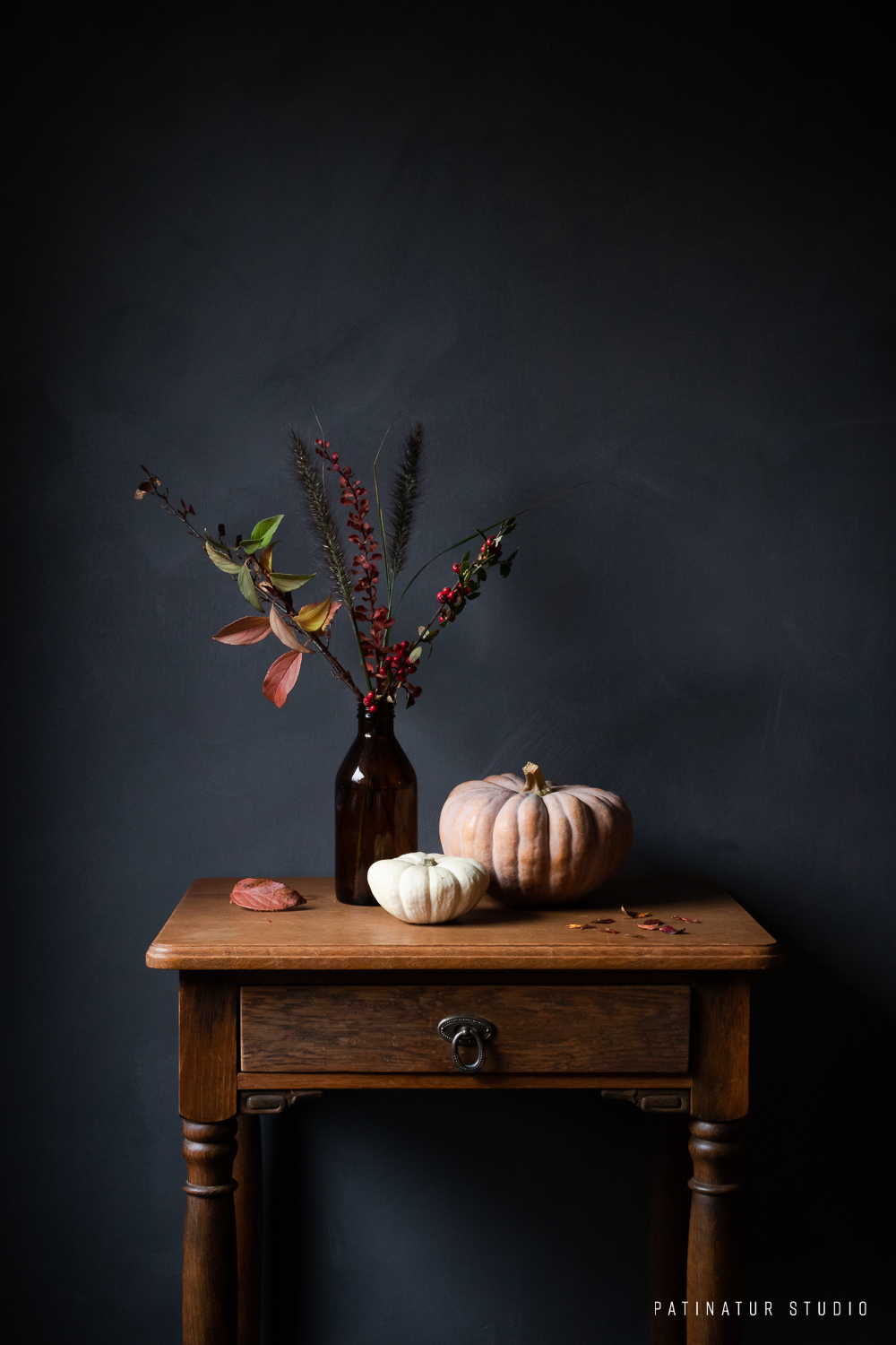 Dark and moody still life photo with autumn bouquet and pumpkins.utumn colours and berries.