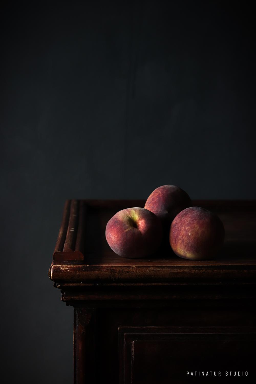 Photo art | Dark and moody still life with 3 peaches on a dark wooden dresser