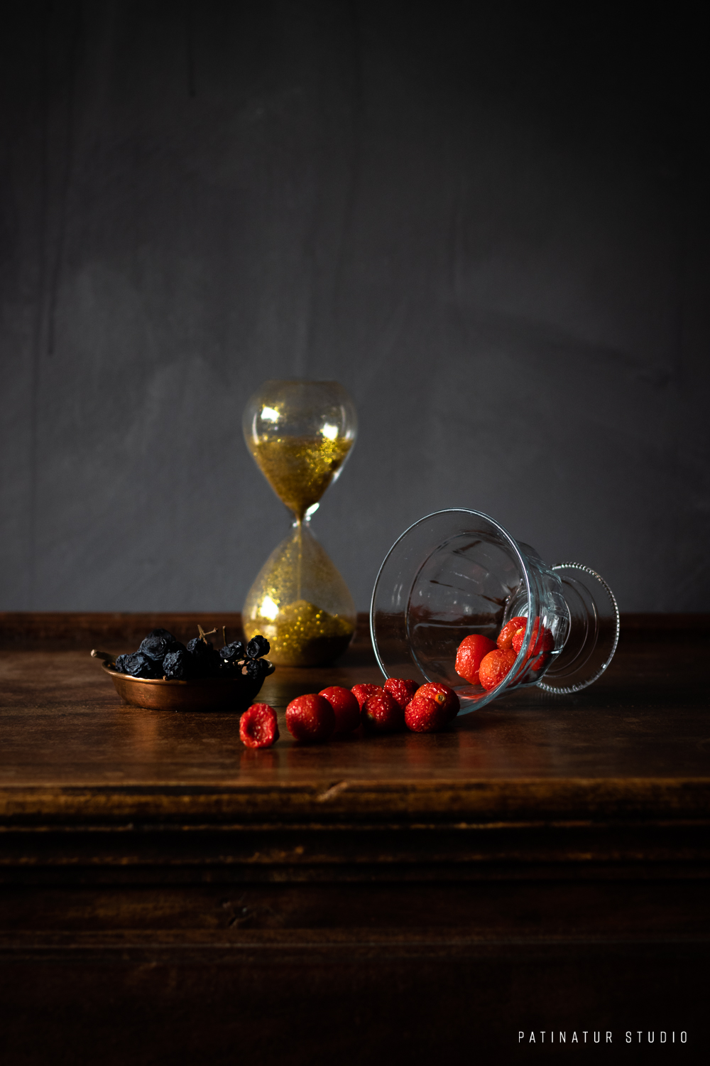 Photo Art | Dark and moody vanitas still life with hourglass and spolied cherry tomatoes and grapes.