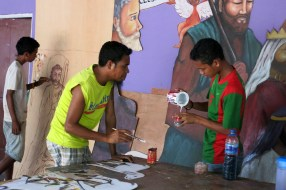 Ino (left) manager of Gembel, the arts collective where I teach English, checks on Rocki's paint-mixing. The young men are making and painting life-size figures for Prezepiu (Nativity scenes) around Dili..