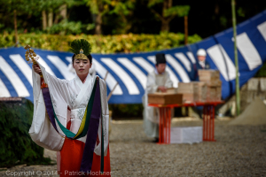 A shrine maiden performing a slow ceremonial dance with bells during the Fushimi Inari Hitakisai ceremony