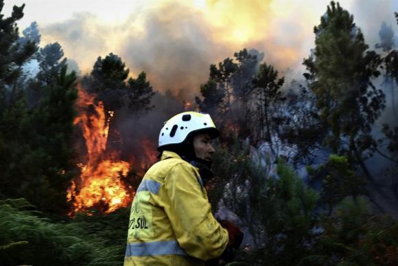 SAO PEDRO DO SUL (PORTUGAL), 21/08/2017.- Un bombero combate las llamas de un incendio declarado en los montes de Manhouce, en Sao Pedro do Sul, Portugal,