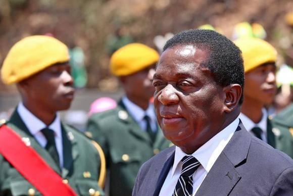 Ex-vice-presidente do Zimbábue e tropas ao fundo