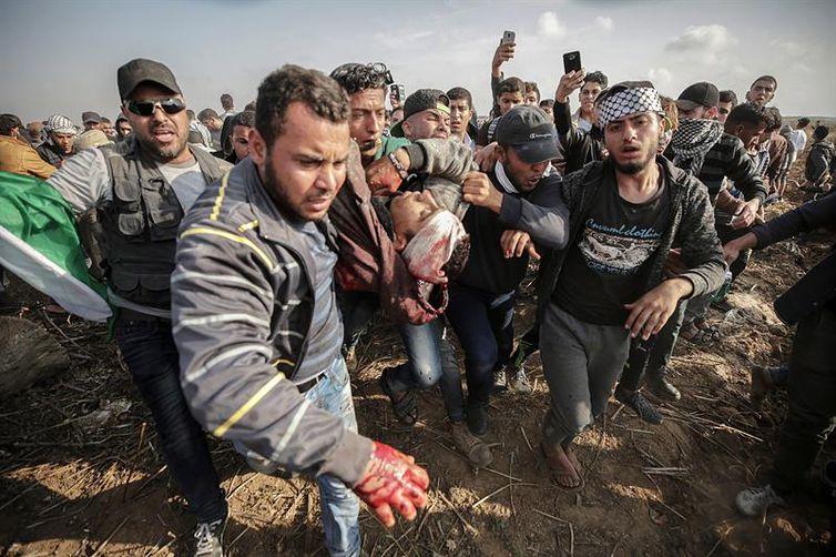 Palestinos ajudam jovem companheiro que morreu durante os enfrentamentos com as tropas do Exército israelense na Faixa de Gaza (Mohammed Saber/Agência EFE/direitos reservados)