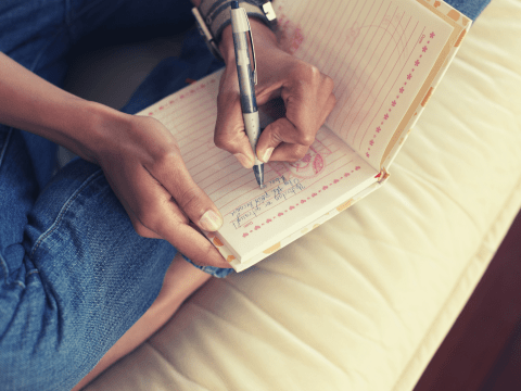 black woman journaling - journal for self-care blog post