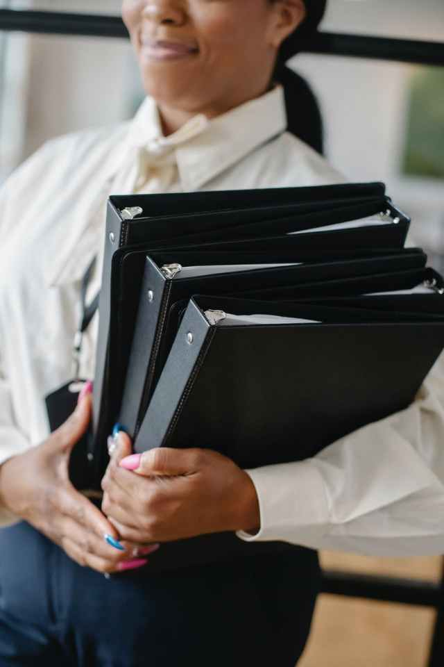 black woman carrying pile of documents in office
