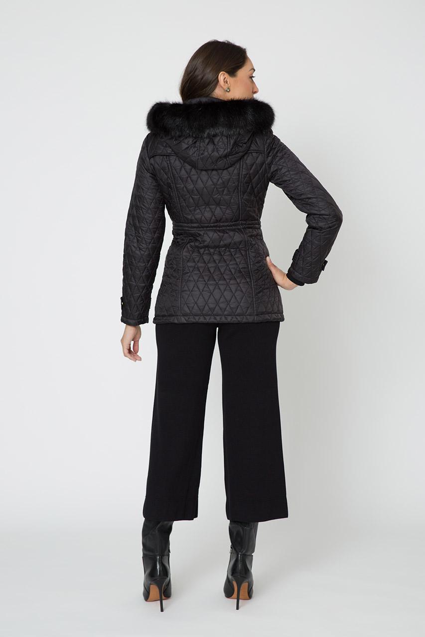 fundo branco com modelo com jaqueta matelasse preta com capuz de pelo