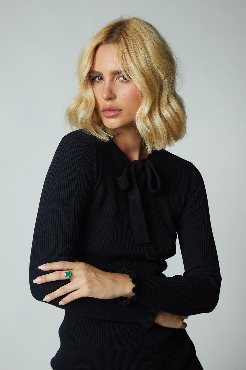 fundo branco com modelo usando blusa de trico com detalhe de laço