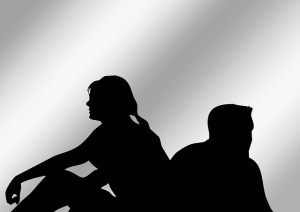 silhouettes of a couple with their backs to each other